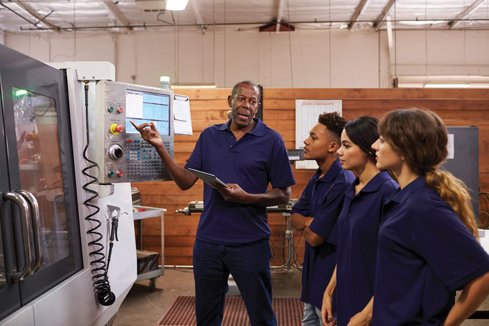 Manufacturing worker training younger employees