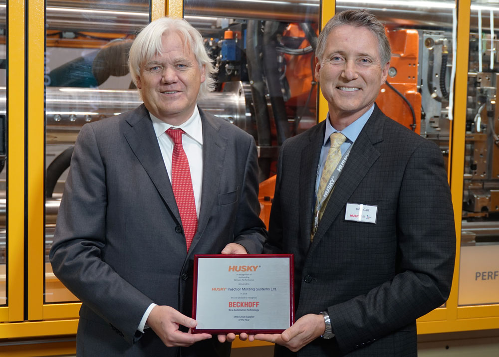 "John Galt (right), president and CEO of Husky Injection Molding Systems, presents the ""EMEA Supplier of the Year"" award to Hans Beckhoff, managing director and owner of Beckhoff Automation, in October 2019 at the K show in Düsseldorf, Germany. Photo: Beckhoff Automation"